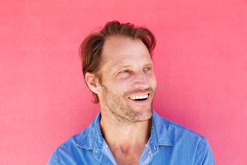 Knappe mens die tegen roze achtergrond lachen stock fotografie