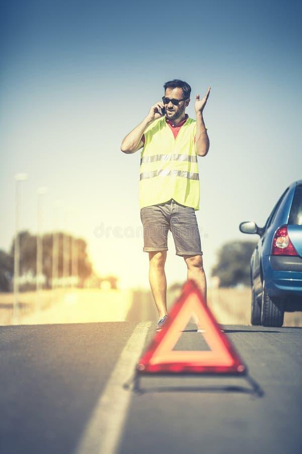 Knappe mens die telefonisch aan de hulp na autoanalyse spreken royalty-vrije stock foto
