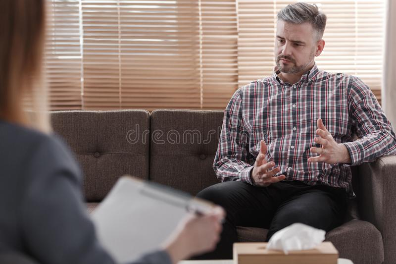 Knappe mens die terwijl het spreken aan zijn psycholoog dur gesticuleren royalty-vrije stock foto