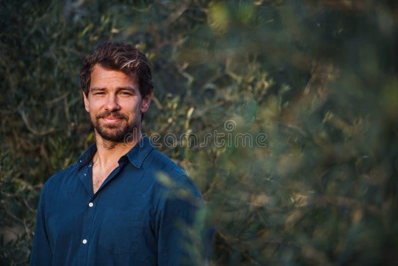 Knappe mens die zich in openlucht door olijfboom bevinden De ruimte van het exemplaar royalty-vrije stock foto