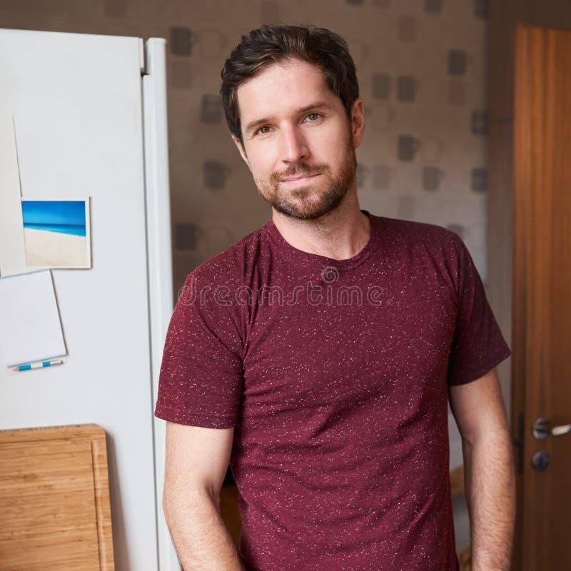 Knappe mens die zich in zijn moderne keuken in de ochtend bevinden stock foto