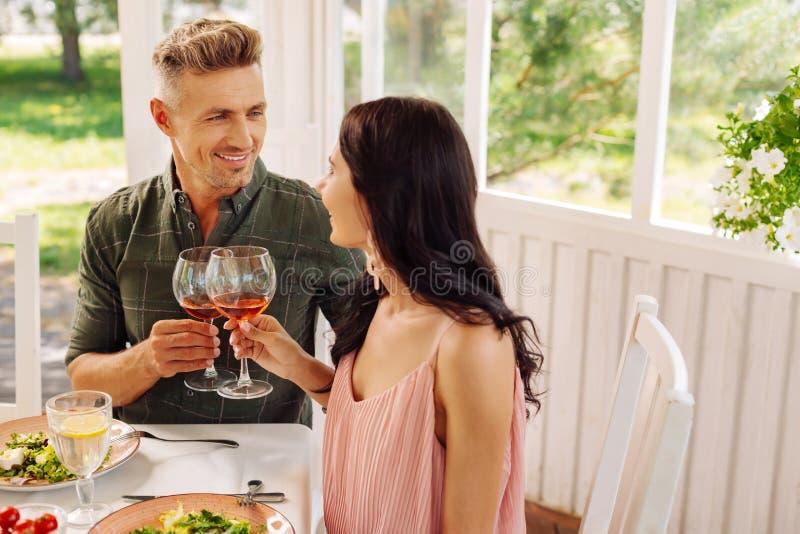 Knappe mens die zijn mooie vrouw bekijken terwijl het drinken van wijn stock foto's