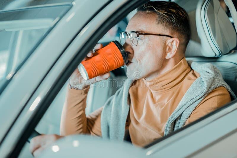 Knappe mens die zijn ochtendkoffie in auto drinken royalty-vrije stock foto