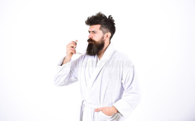 Knappe mens in een badjas die een kop op witte achtergrond houden Gebaarde kerel het drinken koffie of thee in de ochtend stock afbeeldingen