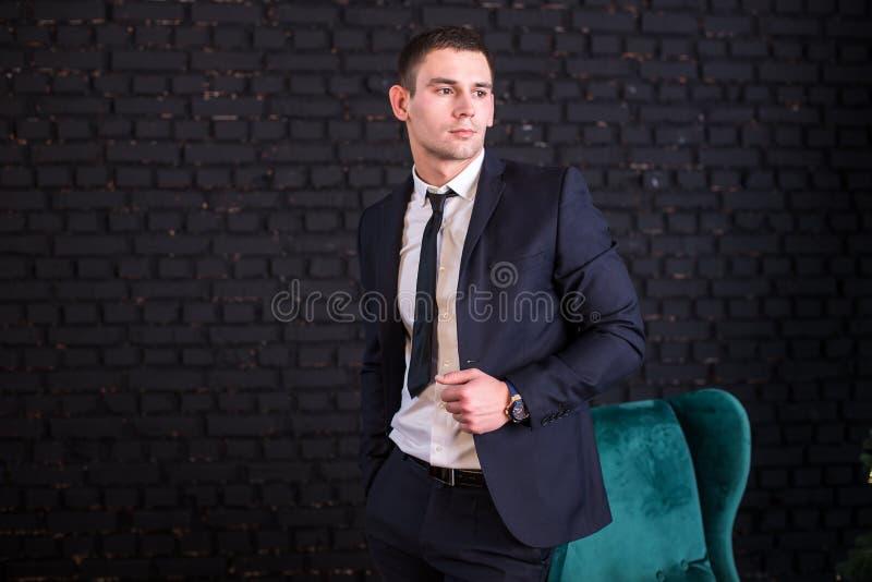 Knappe mens in een pak tegen een zwarte bakstenen muur, modelfoto Succesvolle modieuze mens stock fotografie