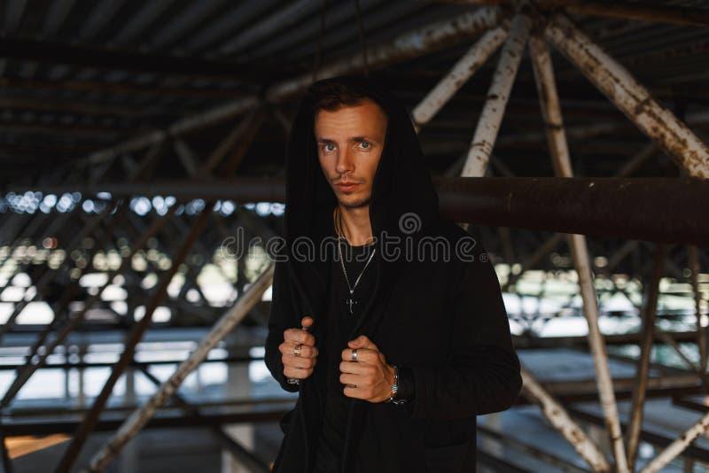 Knappe mens in een zwarte kap dichtbij metaalpijpen royalty-vrije stock foto
