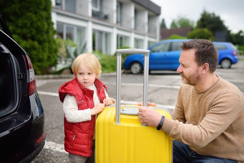 Knappe mens en zijn kleine zoon die naar vakanties gaan, die hun koffer in autoboomstam laden royalty-vrije stock afbeeldingen