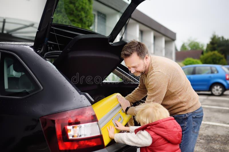 Knappe mens en zijn kleine zoon die naar vakanties gaan, die hun koffer in autoboomstam laden royalty-vrije stock foto's
