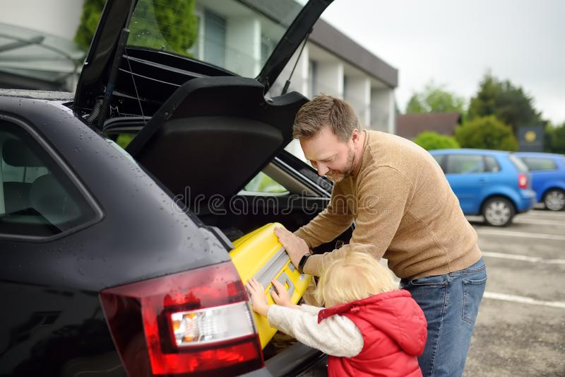 Knappe mens en zijn kleine zoon die naar vakanties gaan, die hun koffer in autoboomstam laden Automobiele reis in het platteland stock afbeelding