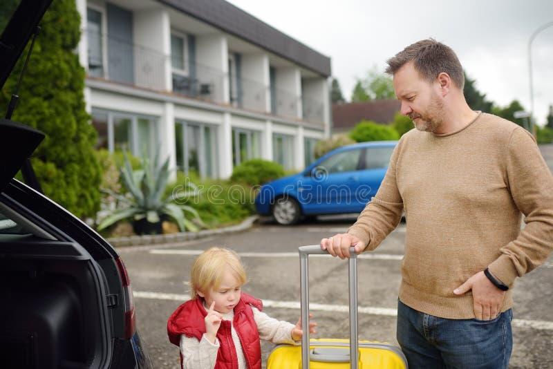 Knappe mens en zijn kleine zoon die naar vakanties gaan, die hun koffer in autoboomstam laden Automobiele reis in het platteland stock foto's
