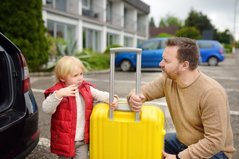 Knappe mens en zijn kleine zoon die naar vakanties gaan, die hun koffer in autoboomstam laden Automobiele reis in het platteland stock afbeeldingen