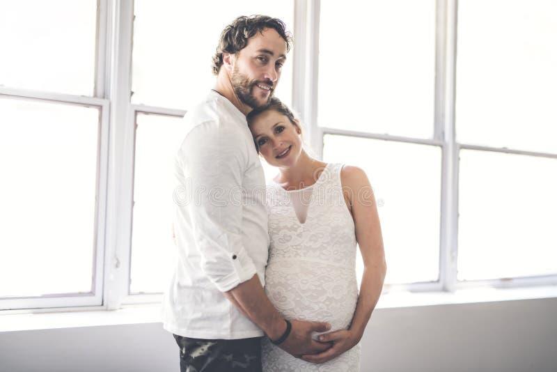 Knappe mens en zijn mooie zwangere vrouw die dichtbij het venster zich thuis bevinden stock afbeelding
