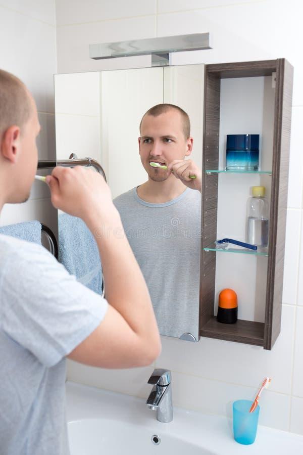 Knappe mens het borstelen tanden en het bekijken spiegel in badkamers stock fotografie