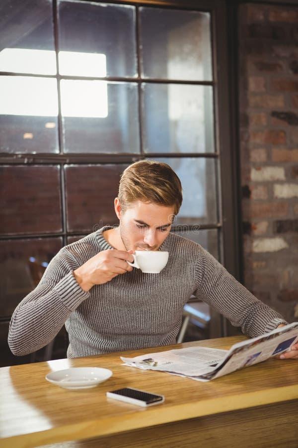 Knappe mens het drinken koffie en het lezen van krant stock afbeelding