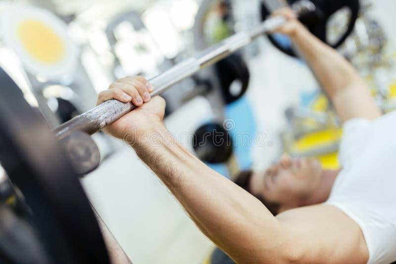 Knappe mens het opheffen gewichten in gymnastiek stock foto's