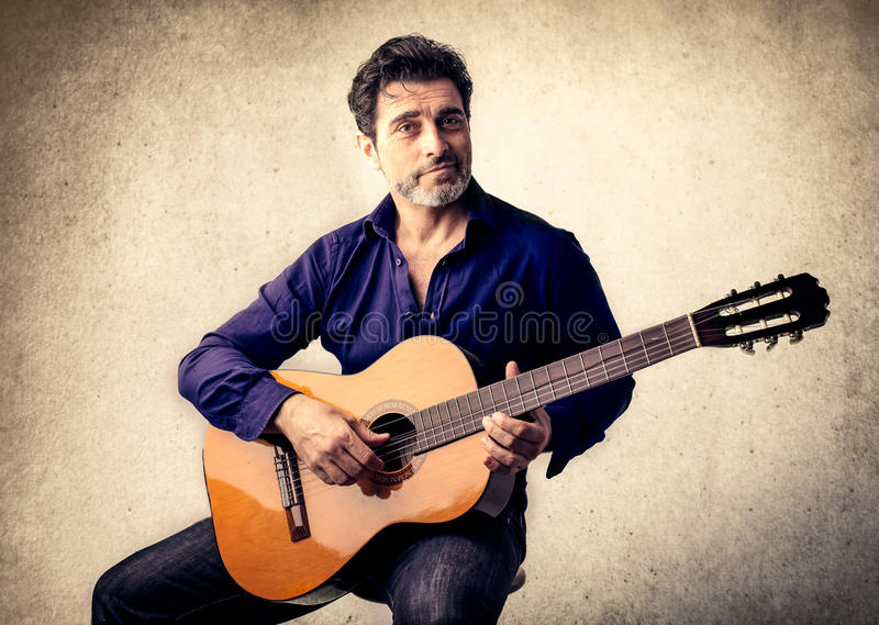 Knappe mens het spelen gitaar stock foto