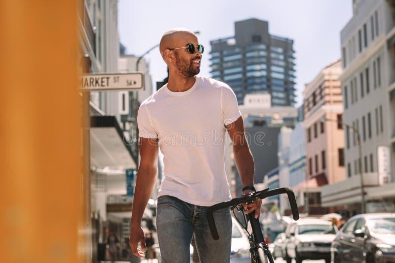 Knappe mens in het toevallige lopen in openlucht met fiets royalty-vrije stock foto's