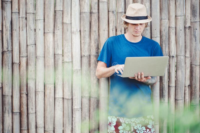 Knappe mens in hoed die met laptop bij de bamboemuur werken royalty-vrije stock foto's