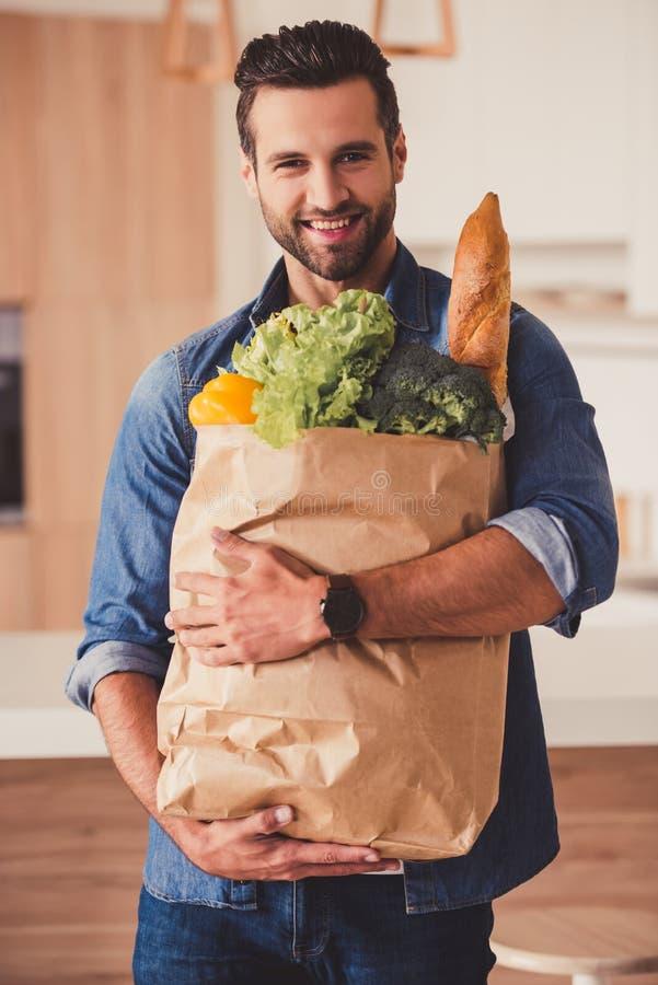 Knappe mens in keuken stock afbeelding
