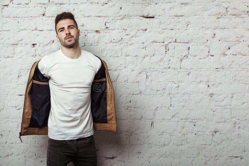 Knappe mens in lege t-shirt die zijn leerjasje, witte bakstenen muurachtergrond opstijgen stock afbeelding