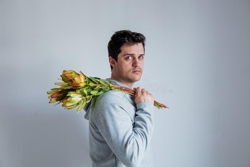 Knappe mens met de bloem van de zonsondergangsafari op grijze achtergrond royalty-vrije stock afbeeldingen