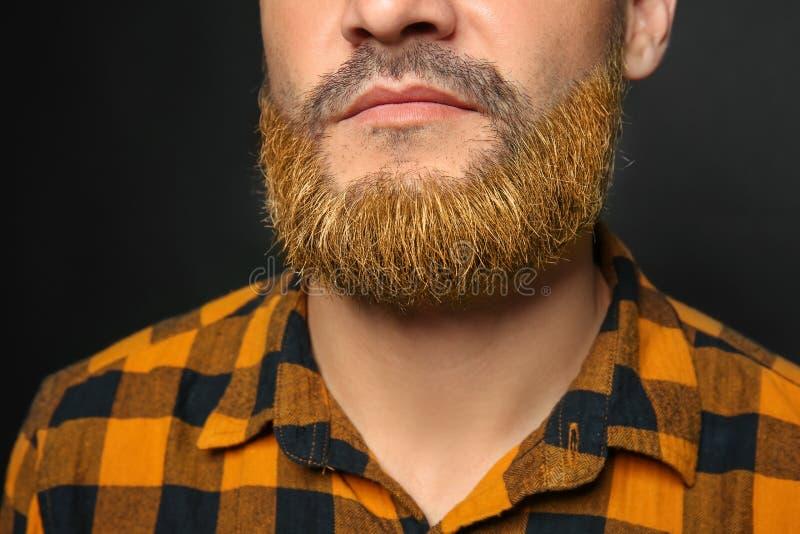 Knappe mens met geverfte baard op donkere achtergrond, close-up stock afbeelding