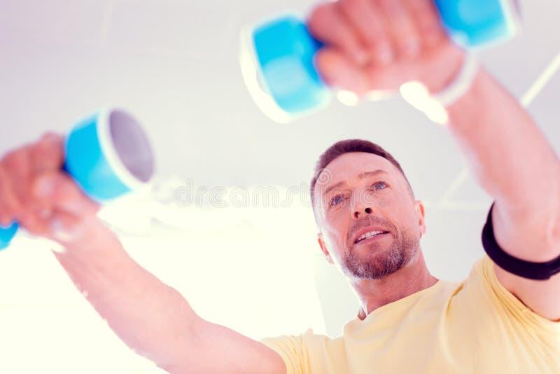 Knappe mens met gezichtsrimpels die ochtendoefening met handgewichten doen royalty-vrije stock fotografie