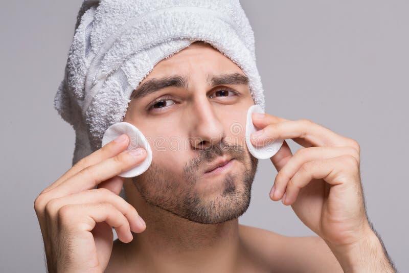Knappe mens met handdoek op hoofd schoonmakend gezicht royalty-vrije stock afbeeldingen