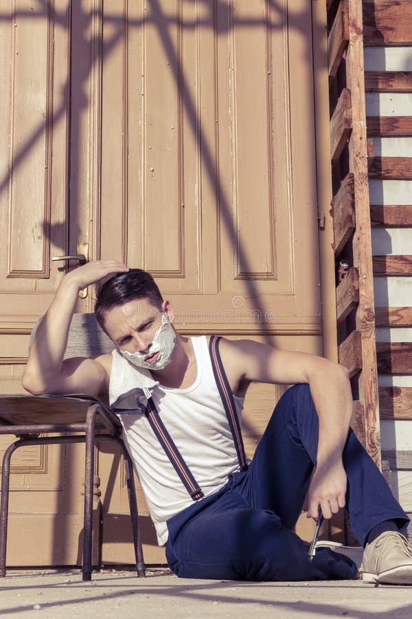 Knappe mens met het scheren van schuim op zijn gezicht en handdoek rond van hem stock afbeeldingen