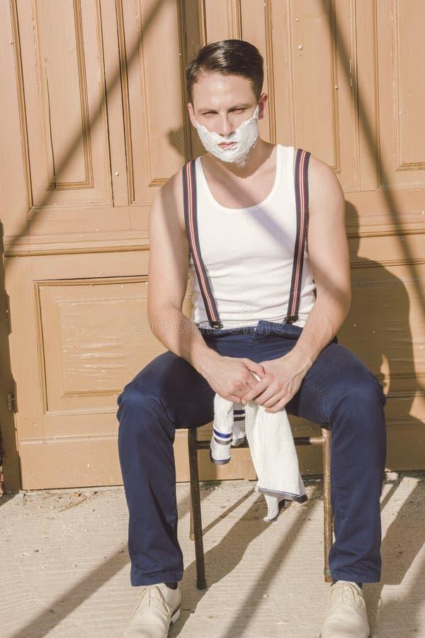 Knappe mens met het scheren van schuim op zijn gezicht en handdoek rond van hem royalty-vrije stock afbeeldingen