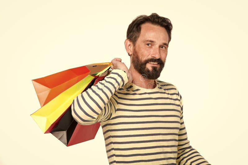 Knappe mens met kleurrijke die document zakken op wit wordt geïsoleerd Mens in marine die misstap-over- het winkelen zakken drage stock foto
