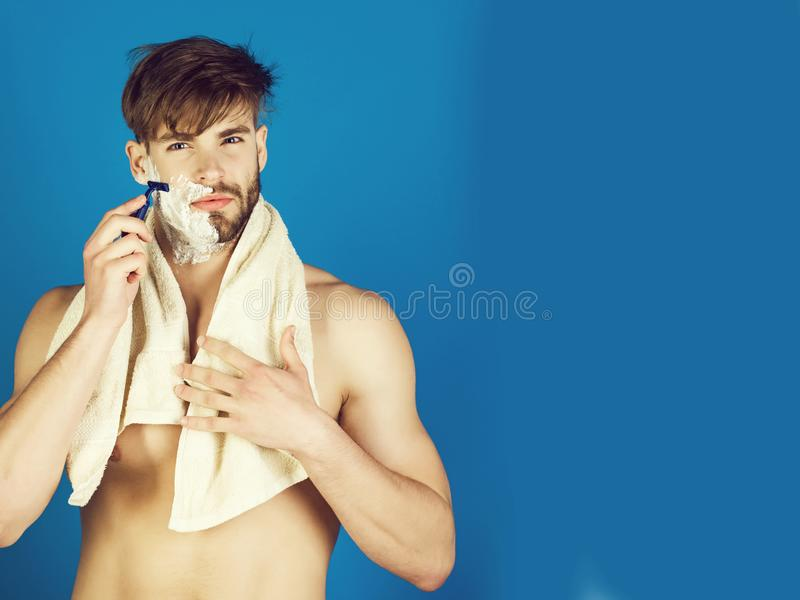 Knappe mens met naakte torso het scheren baard met veiligheidsscheermes stock foto