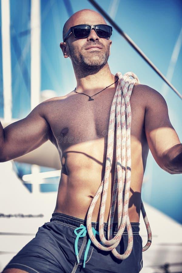 Knappe mens op zeilboot stock foto