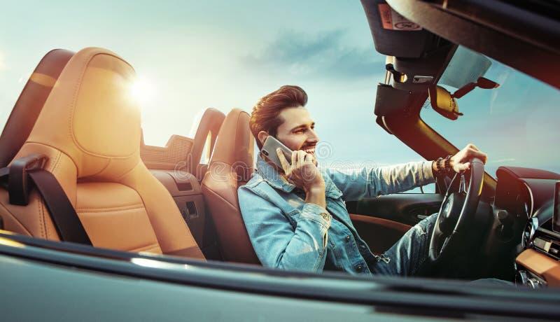 Knappe mens riridng een convertibele auto stock foto