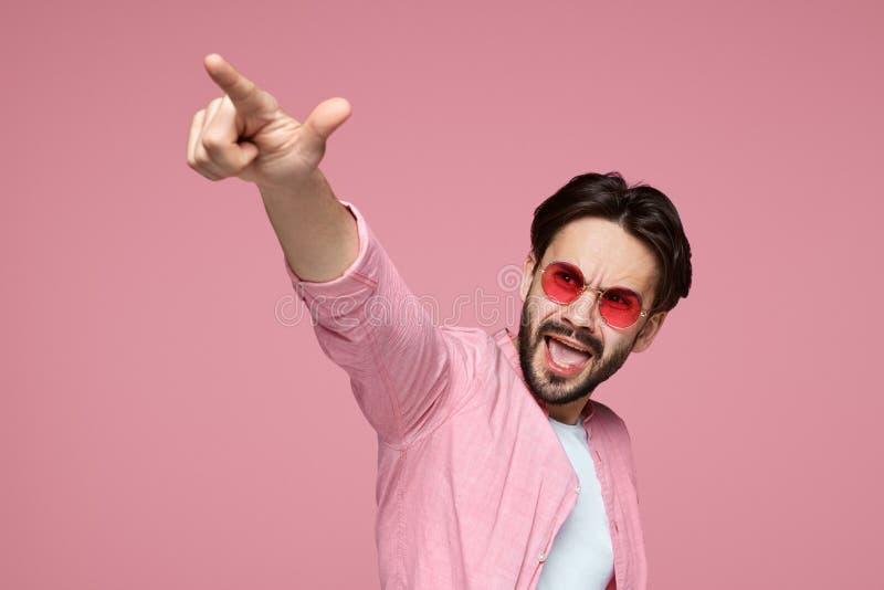 Knappe mens in roze overhemd die vinger richten op camera, en zich over roze achtergrond gillen bevinden royalty-vrije stock fotografie