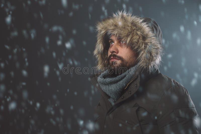Knappe mens in sneeuwonweer stock fotografie