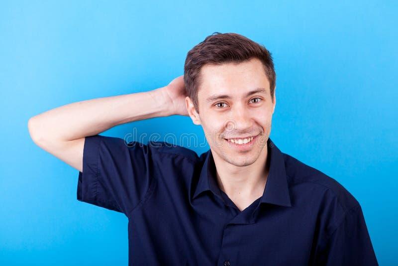 Knappe mens in toevallig overhemd op blauwe achtergrond stock fotografie