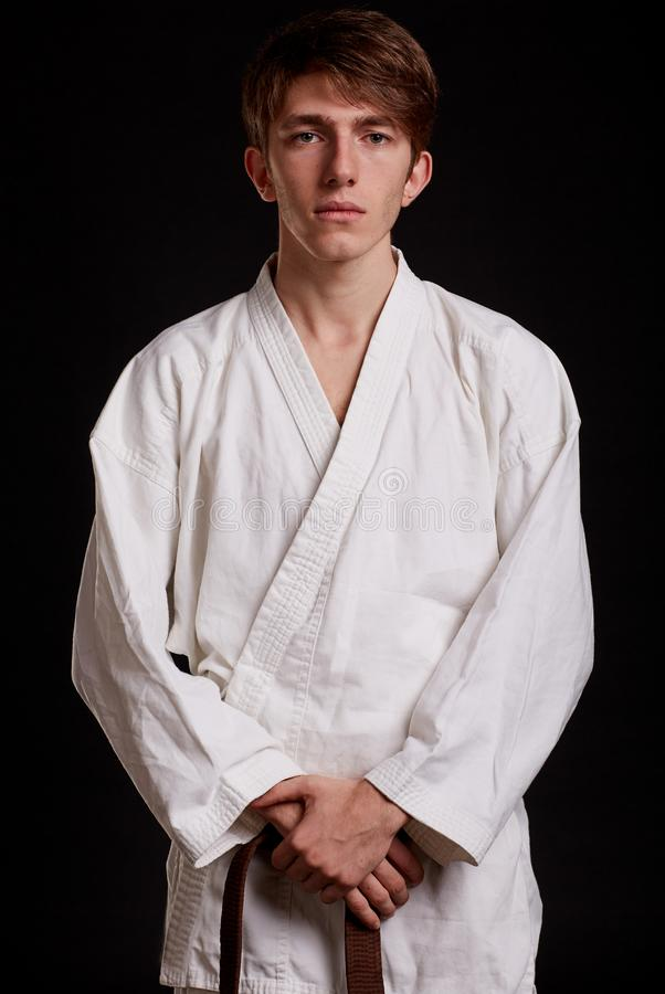 Knappe mens in witte kimono op een zwarte achtergrond Jongen het leren het vechten technieken Het concept van karatelessen stock afbeeldingen