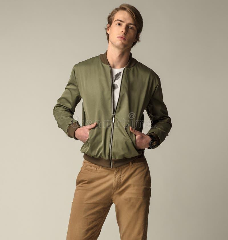 Knappe mensen die groen jasje en bruine broeken dragen stock afbeelding