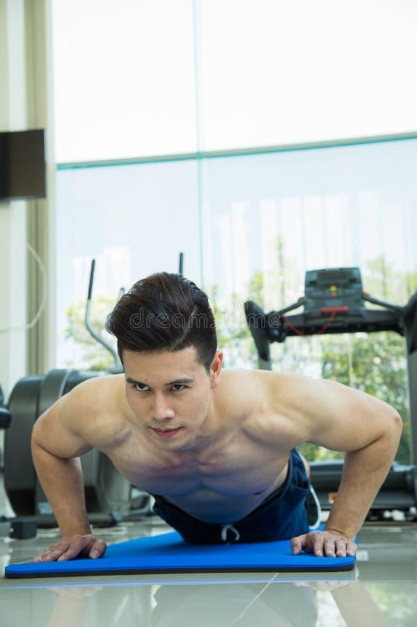 Knappe mensenfitness die door duw UPS te doen als deel van het bodybuilding van opleiding in het fitness centrum uitoefenen, spor royalty-vrije stock fotografie
