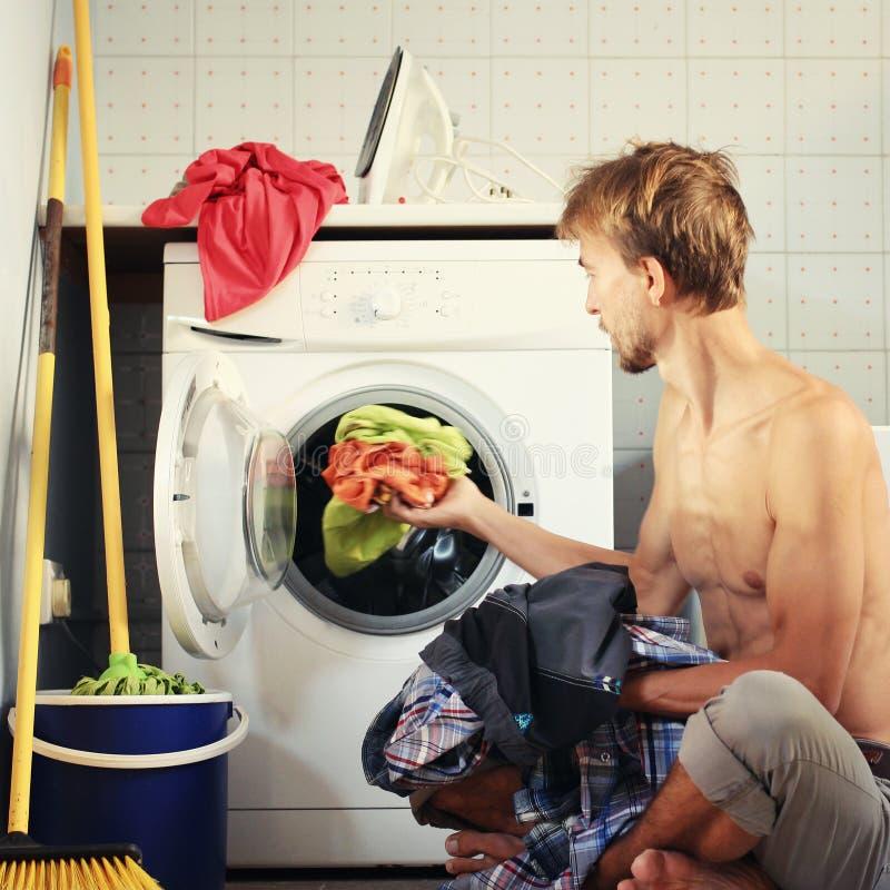 Knappe mensenladingen in de wasmachine vuile kleren Vrijgezelhuishoudelijk werk, mannelijk huisvrouwenconcept stock foto