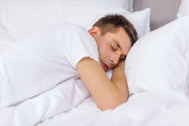 Knappe mensenslaap in bed royalty-vrije stock foto's