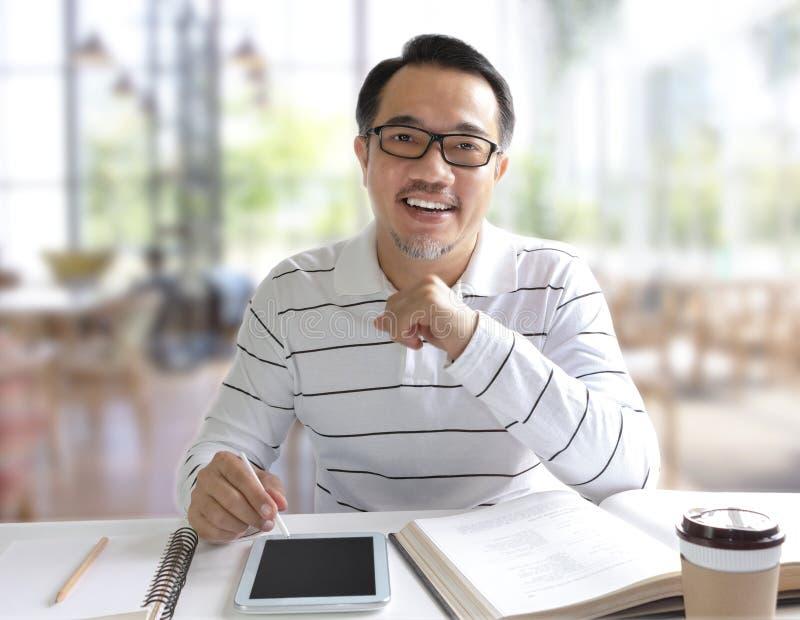 Knappe mensenzitting in de koffiewinkel en het schrijven op digitaal royalty-vrije stock afbeeldingen