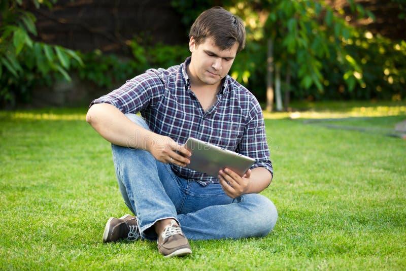 Knappe mensenzitting op gras bij park en het gebruiken van digitale tablet stock afbeelding
