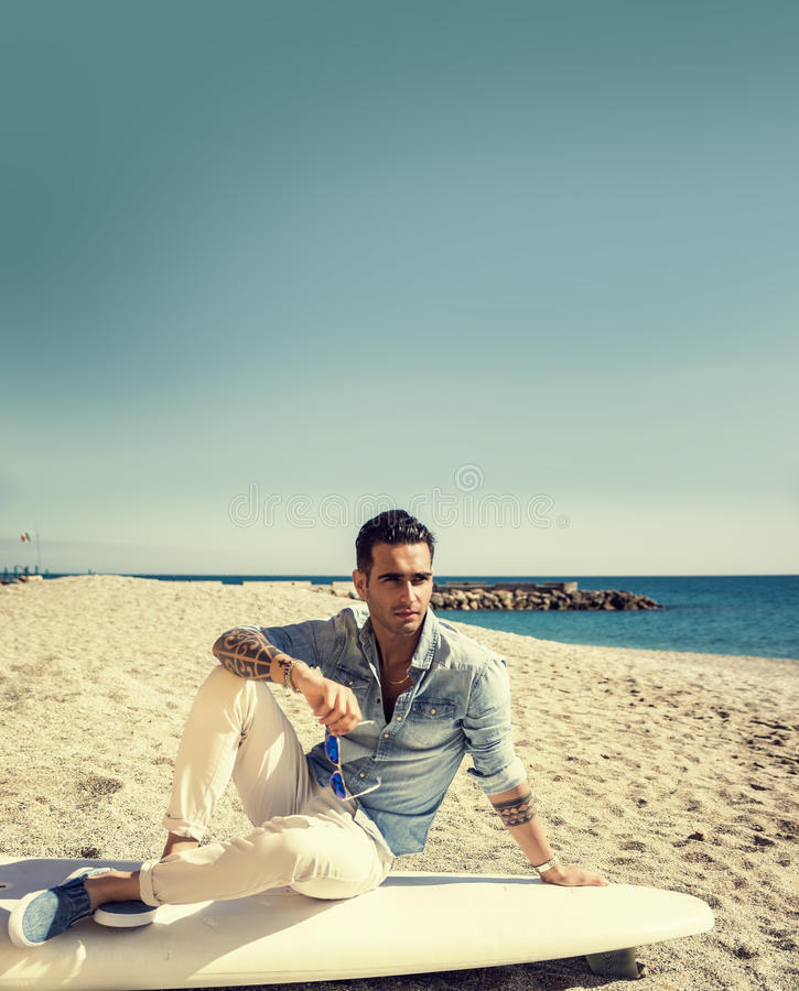 Knappe mensenzitting op surfplank bij strand stock foto's