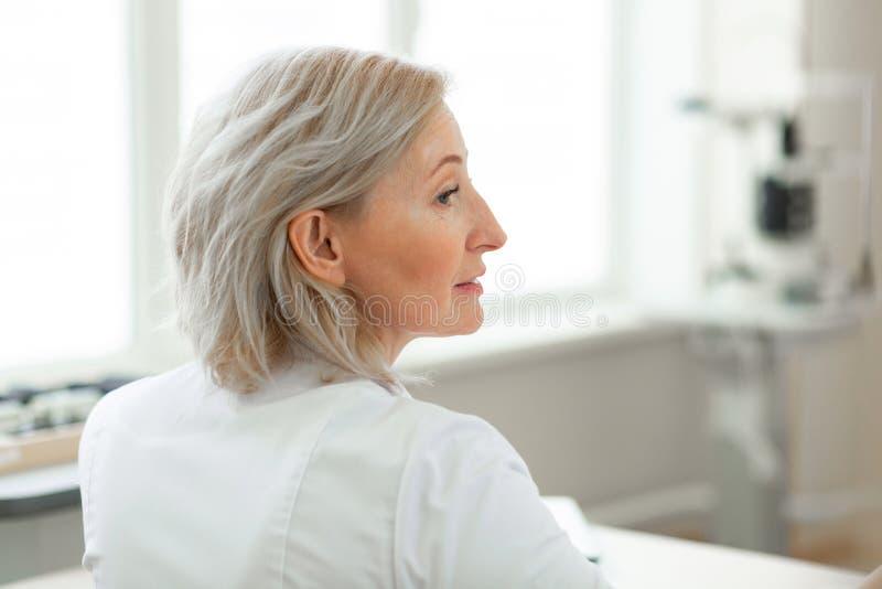 Knappe midden-leeftijdsoftalmoloog die intense werkdag hebben stock afbeeldingen