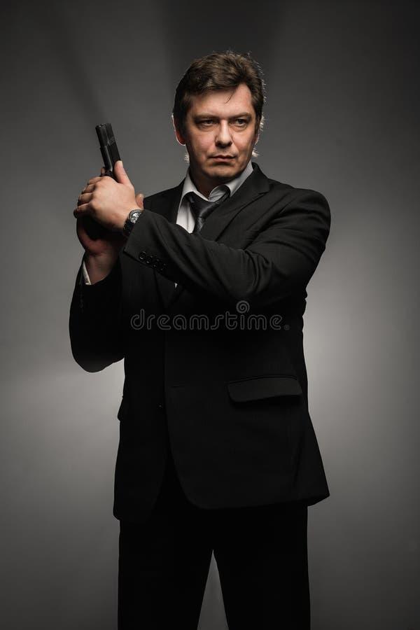 Knappe midden oude detectivemens met kanon op donkere achtergrond stock fotografie
