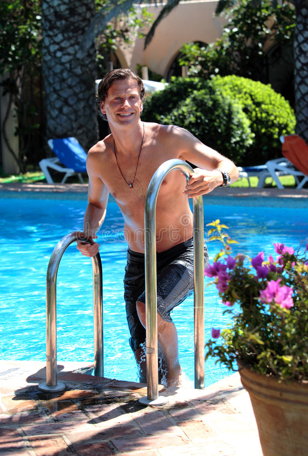 Knappe midden oude mens die uit zwembad beklimt royalty-vrije stock foto's
