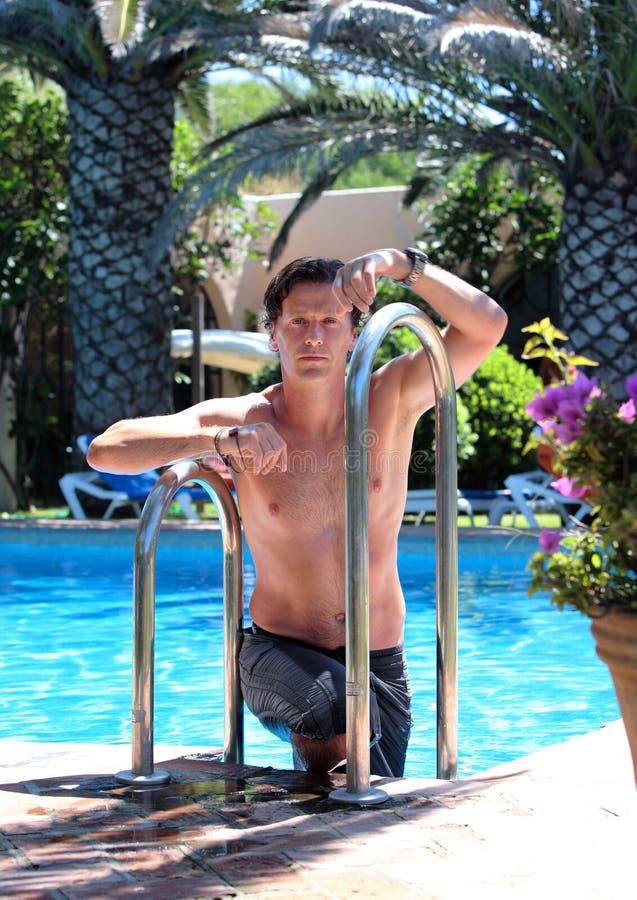 Knappe midden oude mens die uit zwembad beklimt royalty-vrije stock fotografie