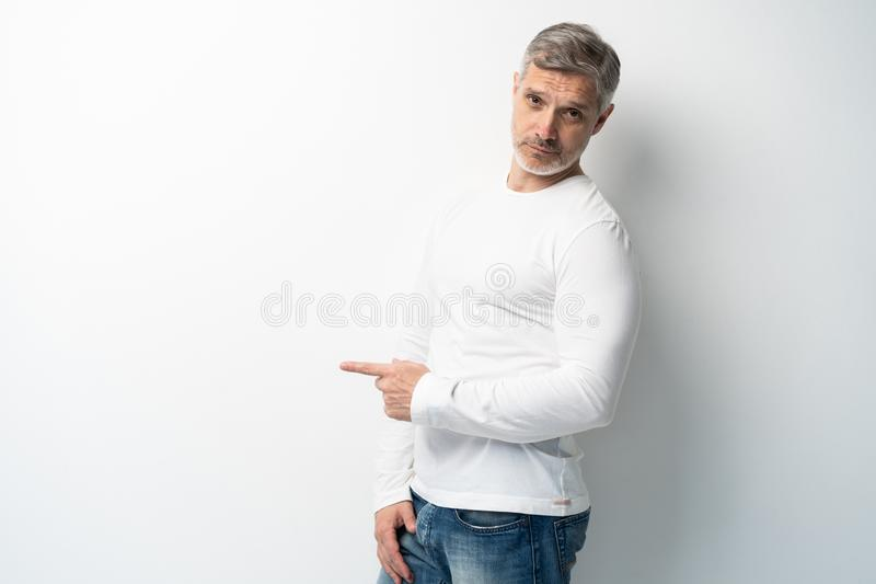 Knappe middenleeftijds hogere mens die en met palm van hand voorstellen richten die de camera over witte achtergrond bekijken royalty-vrije stock afbeeldingen
